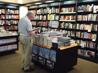 Image of the inside of a bookstore, with shelves along the wall and also tables covered in books.