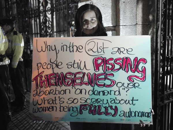 """A woman holds a placard saying """"Why in the 21st Century are people still PISSING THEMSELVES over abortion on demand? What's so scary about women being FULLY autonomous?"""""""
