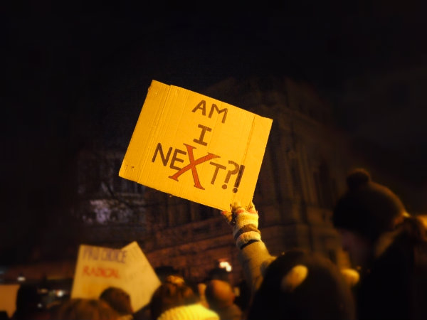 "A gloved hand holds up a sign saying ""Am I NeXt?"""