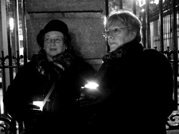 Two people hold candles outside the gates of Leinster House
