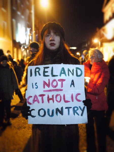 "A woman holding a sign saying ""Ireland is not a Catholic country"""
