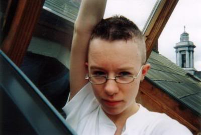 Picture of me at 19-ish: a young person with a mostly-shaved head and wonky glasses looking out of an attic window.